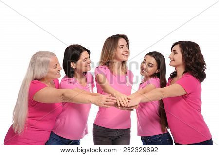 Group Of Women With Silk Ribbons Joining Hands On White Background. Breast Cancer Awareness Concept