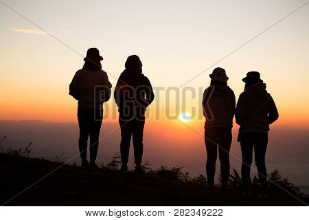 Silhouette Of Young Woman Are Standing On Top Of The Mountain Relaxing With Sunrise By Nature At Sun