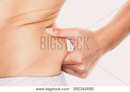 Love handle woman pinching fat on hips around waist - weight loss diet concept.