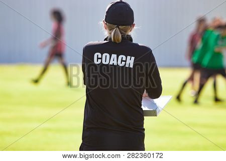 Back View Of Female Football Coach In Black Coach Shirt At An Outdoor Sport Field Watching Her Team