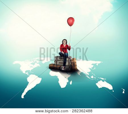 Happy Woman Holds A Red Balloon Sitting On Luggages On World Map.