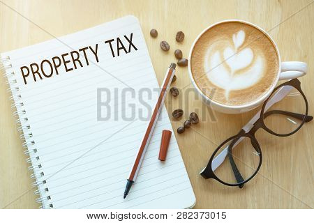 Property Tax Concept On Notebook With Glasses, Pencil And Coffee Cup On Wooden Table. Business Conce