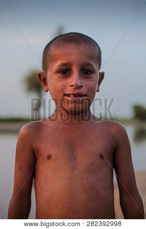 Portrait Of A Nacked Village Boy Smiling And Looking At Camera In Sindh Moro