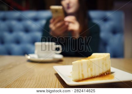 Blurred Of Unknown Girl With Phone And Cup Of Coffee. Selective Focus On The Cheesecake, Close Up
