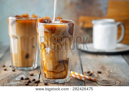 Ice Coffee In A Tall Glass With Cream Poured Over, Coffee Ice Cubes And Beans On A Old Rustic Wooden