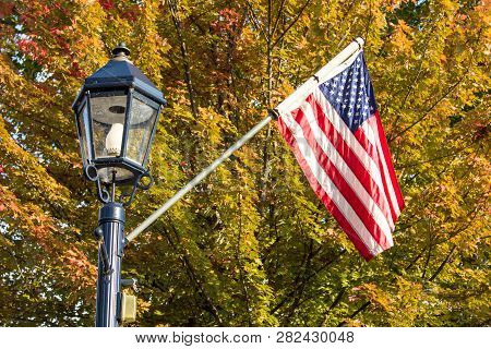 Small Town Usa. Main Street Lamppost And American Flag Set Against Beautiful Fall Foliage In The Mid