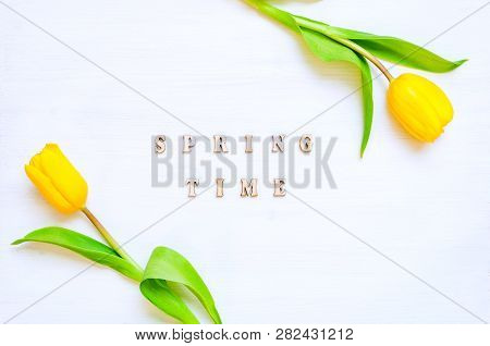 Spring flower background - composition made of spring yellow tulip flowers and wooden inscription Spring time on the white background. Flat lay, top view, space for text. Spring composition