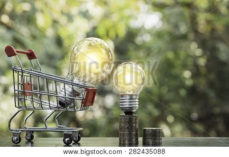 Energy Saving Light Bulb With Stacks Of Coins And Shopping Cart For Saving, Financial And Shopping C