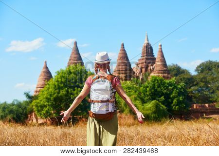 Rear View Of Woman Traveler With A Backpack Walking Through The Field To The Ancient Buddhist Stupas