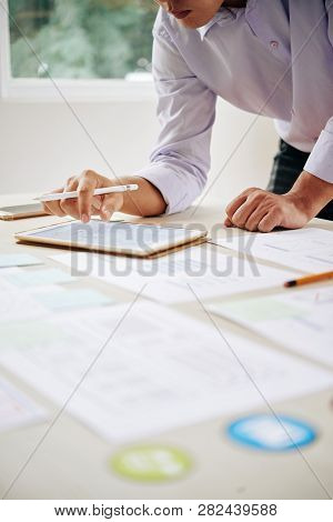 Young Businessman Bending Over Workplace While Scrolling Through Digital Data In Touchpad And Analyz
