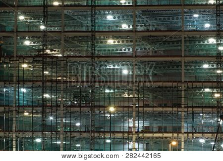 a full frame view of a large construction site at night illuminated by bright work lights with girders and construction hoists poster