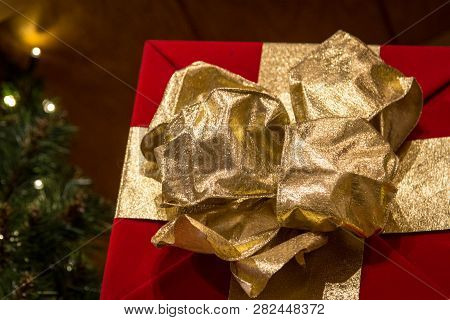 Christmas Morning. Close Up Of Wrapped Christmas Gift With Red Paper And An Ornate Gold Bow With Whi