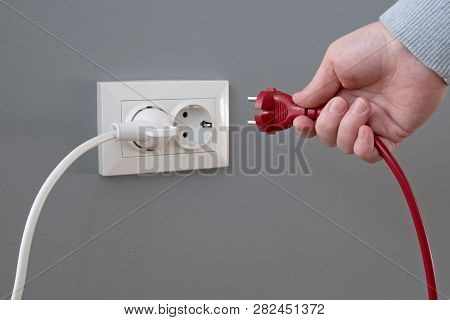 Hand plugging in an electric cord into a white plastic socket or  european wall outlet on grey plaster wall. Closeup of a woman's hand inserting an electrical plug into a wall socket. Daylight. poster