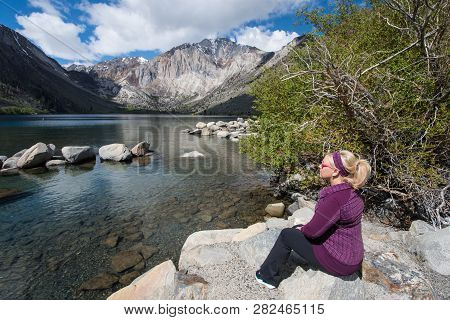 Blond Female Sits Alone By Convict Lake In The Springtime, Located Off Of Us-395, Near Mammoth Lakes