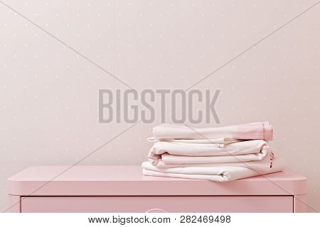 On the dresser is a stack of clean ironed bed linen. Household poster