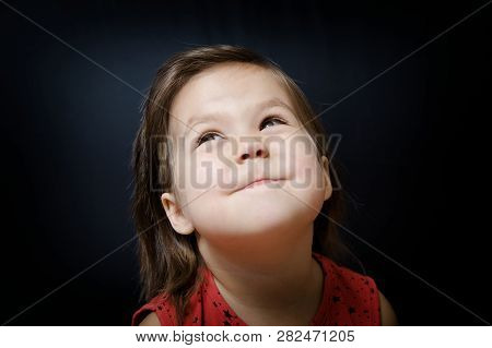Child Looking Up On Dark Background. Little Girl Smiling And Looking At Something Amazing