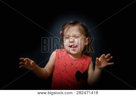 Child Having Fun And Showing Tongue On Dark Background. Funny Little Girl Dancing In The Darkness