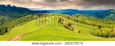 Panorama Of A Beautiful Countryside In Mountains. Path Down The Grassy Rural Hills Rolling In To The
