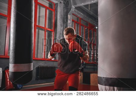 Impossible Is Nothing. Muscular Sportsman In Sport Clothing Exercising On Heavy Punch Bag Before Fig