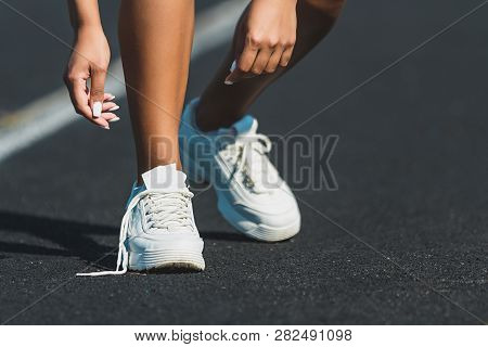 Woman Runner Tying Shoelace On Running Track, Athlete To Tie Her Shoes