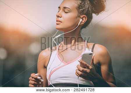 Serious Female Jogger Looking Confident. Young Fitness Woman Listening Music With Headphones After T