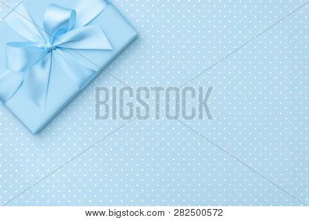 Gift box with blue ribbon bow on blue speckled background top view. Holiday concept, birthday gift, 8 march or Women day, gift box presents holiday Mothers day. Copy space. Flat Lay. poster