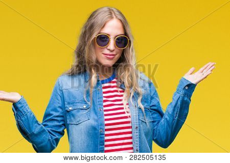 Beautiful young blonde woman wearing sunglasses over isolated background clueless and confused expression with arms and hands raised. Doubt concept.