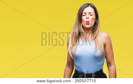 Young beautiful elegant business woman over isolated background puffing cheeks with funny face. Mouth inflated with air, crazy expression.