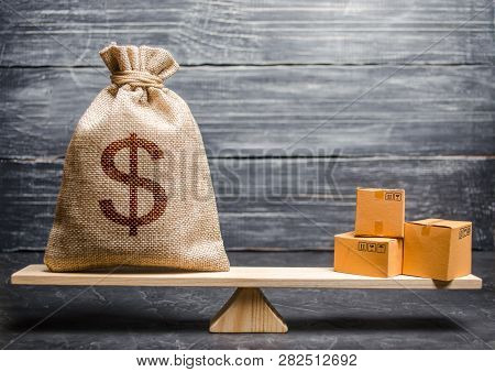A Bag Of Money And A Bunch Of Boxes On The Scales. Conceptual Trade Balance Between Countries And Un