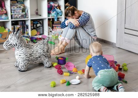 Tired Of Everyday Household Mother Sitting On Floor With Hands On Face. Kid Playing In Messy Room. S