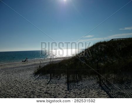 The Sun Casts Darkness On The Dunes Along The Gulf Coast In Florida.