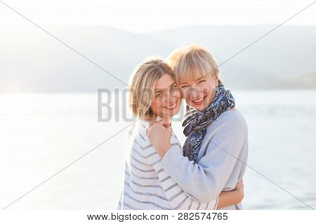 Mother And Her Adult Daughter Are Hugging. Beautiful Women Are Smiling On Sea Beach. Happy Senior Wo