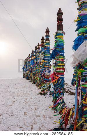 Wooden Ritual Pillars With Colorful Ribbons On Cape Burkhan, Lake Baikal, Olkhon Island, Siberia, Ru