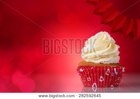 Happy Valentines Day. Delicious Vanilla Cupcake With Butter Cream On A Red Background