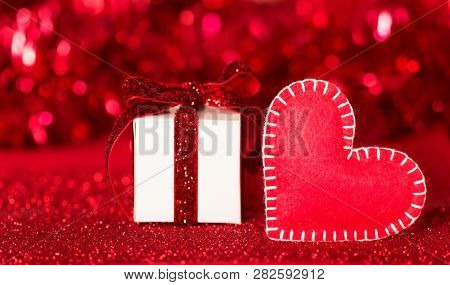 Beautiful Handmade Heart Made Of Felt And A Box With A Gift Ribbon On A Bright Sparkling Red Backgro