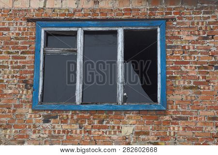 Old Broken Window On Brown Brick Wall Of A House