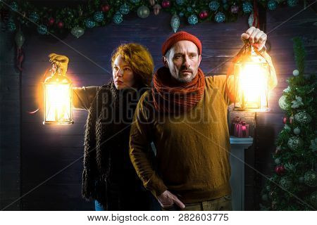 On The Alert. Watchful Couple Holding Vintage Lanterns While Expressing Attention And Scrutinizing W
