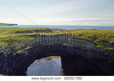 The Bridge Of Ross. A Natural Bridge Formed By The Ross Sandstone Of Carboniferous Age. County Clare