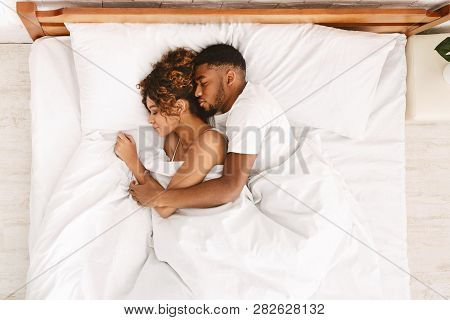 Loving African-american Couple Sleeping In Bed And Hugging, Love And Tenderness Concept, Top View
