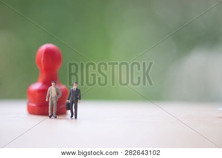 Miniature People: Two Miniature Businessman Standing With Red Pawn Go To Negotiations