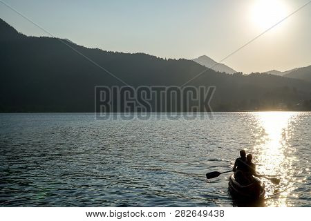 Silhouette Of Happiness Family And Dog Travel To Kayaking Or Canoe On Beautiful Scenery Lake With Su