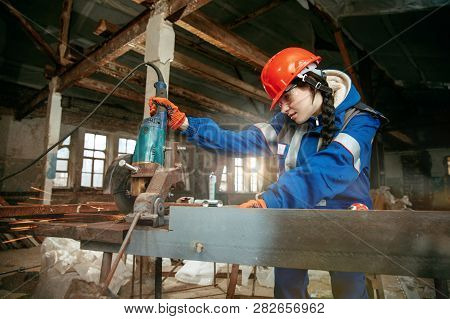 Destroying gender stereotypes. Woman wearing helmet using different male work tools. Gender equality. Girl working at flat remodeling. Building, repair and renovation. woman in the male profession poster