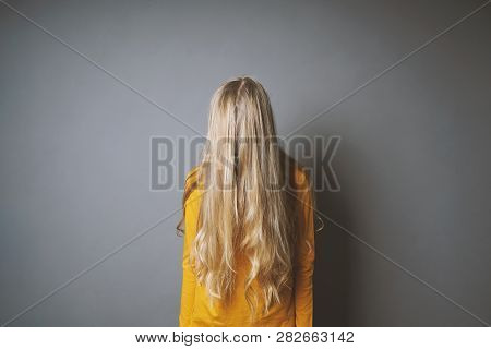 Depressed Young Woman Hiding Her Face Behind Long Blond Hair - Shy Or Indifferent Teenage Girl
