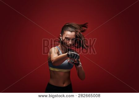 Hustle To Gain More Muscle. Sportswoman Standing Concentrated In Gym Gloves Over Red Background.