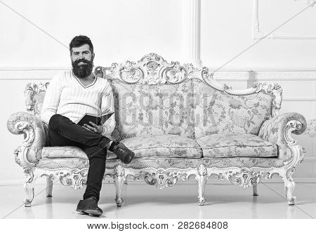 Man With Beard And Mustache Sits On Baroque Style Sofa, Holds Book, White Wall Background. Guy Readi