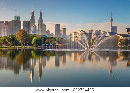 Panoramic view of Kuala Lumpur city waterfront skyline with reflections and beautiful morning sky, Titiwangsa Park, Malaysia. Hight resolutions Kuala Lumpur / Malaysia - February, 25, 2018