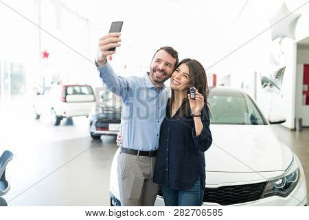 Hispanic Couple Photographing Themselves To Post On Social Media While Standing By New Car In Showro