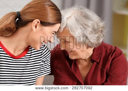 Elderly Woman With Female Caregiver On Blurred Background