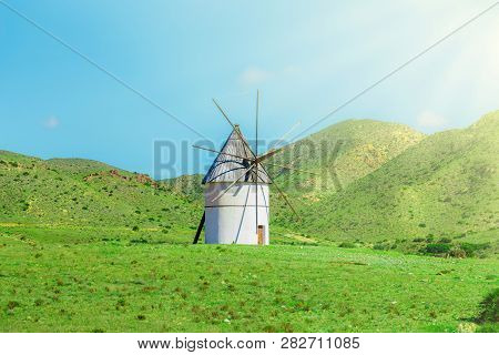 Traditional Windmill On The Green Lawn And Hills, Cabo De Gato, Spain