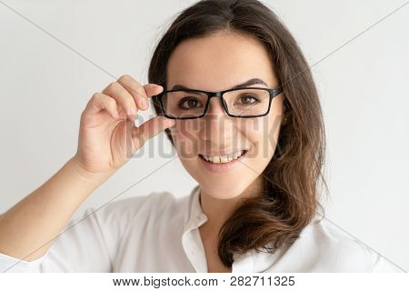 f4b6f58060b Smiling young woman adjusting glasses and looking at camera. Positive pretty  woman touching glasses. Smart woman concept. Isolated front view on white  ...